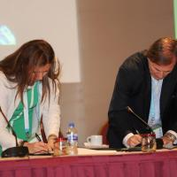 a man and a woman sign documents on a table