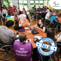 a group of Para athletes having a discussion round a table