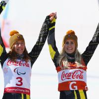 a female vision impaired skier and her guide raise their arms in celebration