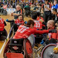 a group of Japanese wheelchair rugby players celebrate on the court