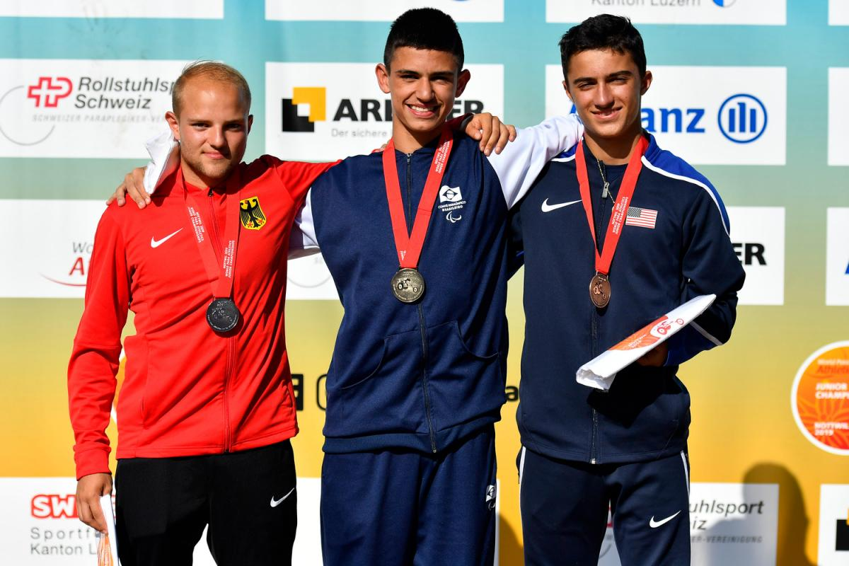 Three young men on a podium with their medals