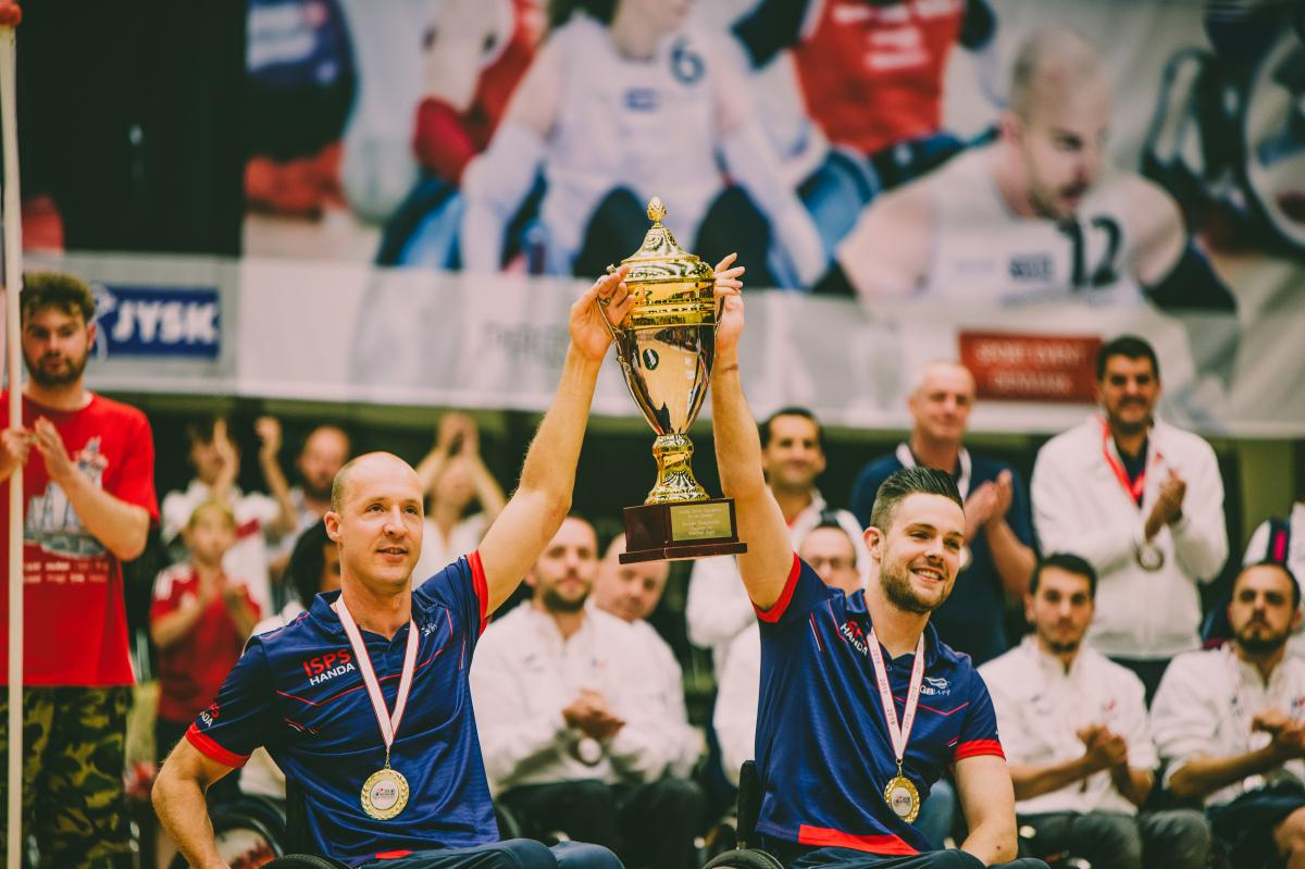 two male wheelchair rugby players with medals around their neck lift a gold cup into the air