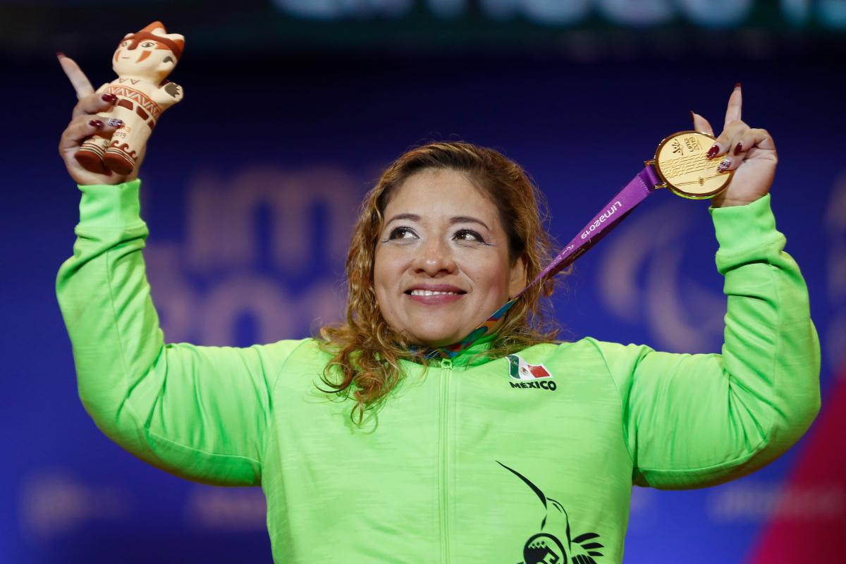 a female powerlifter holds up her gold medal and points her fingers to the sky
