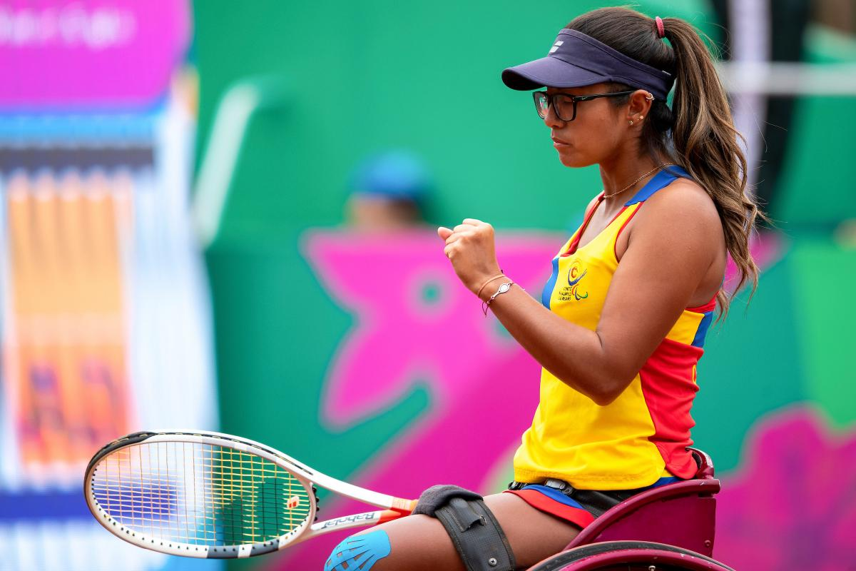 a female wheelchair tennis player clenches her fist on the court