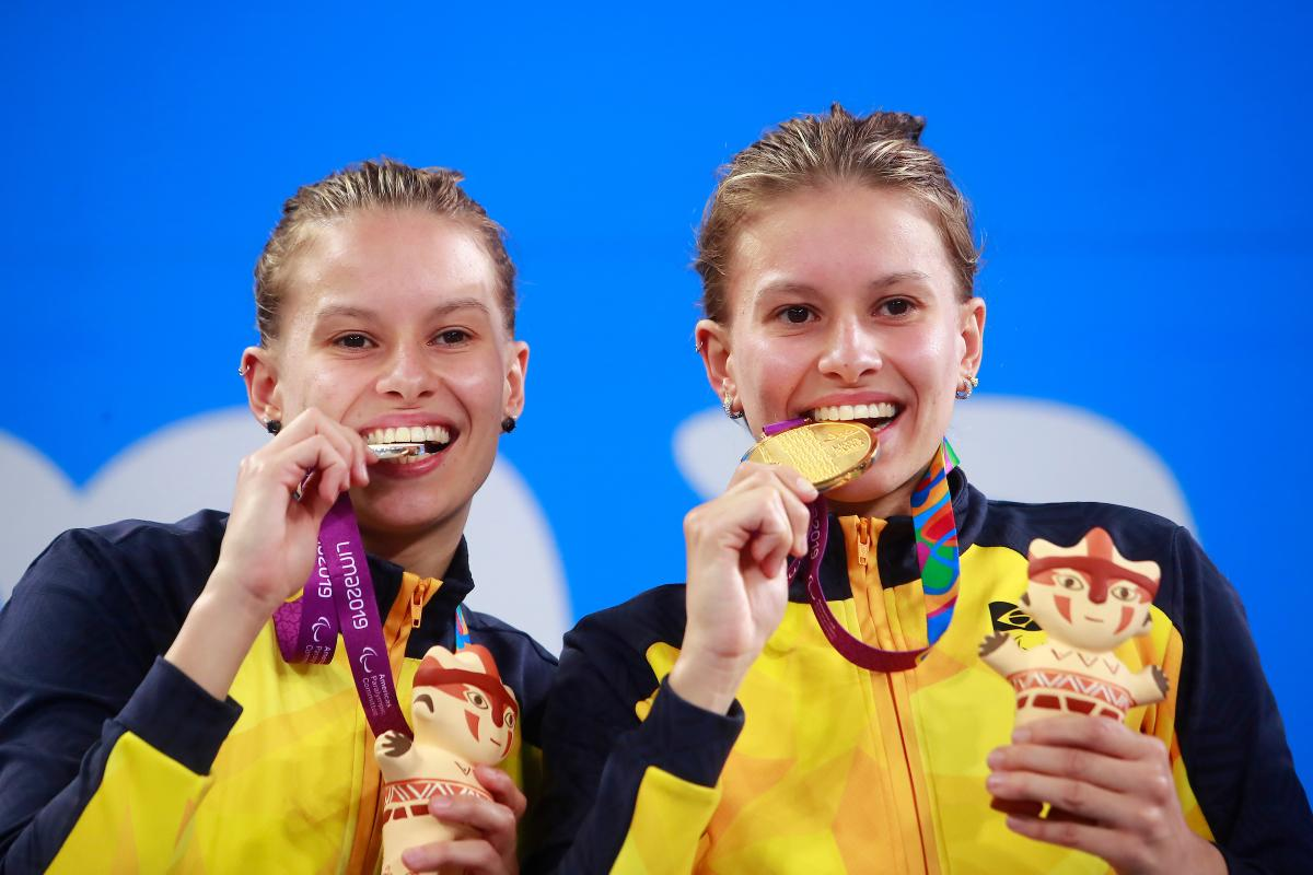 two female Para swimmers on the podium biting their medals