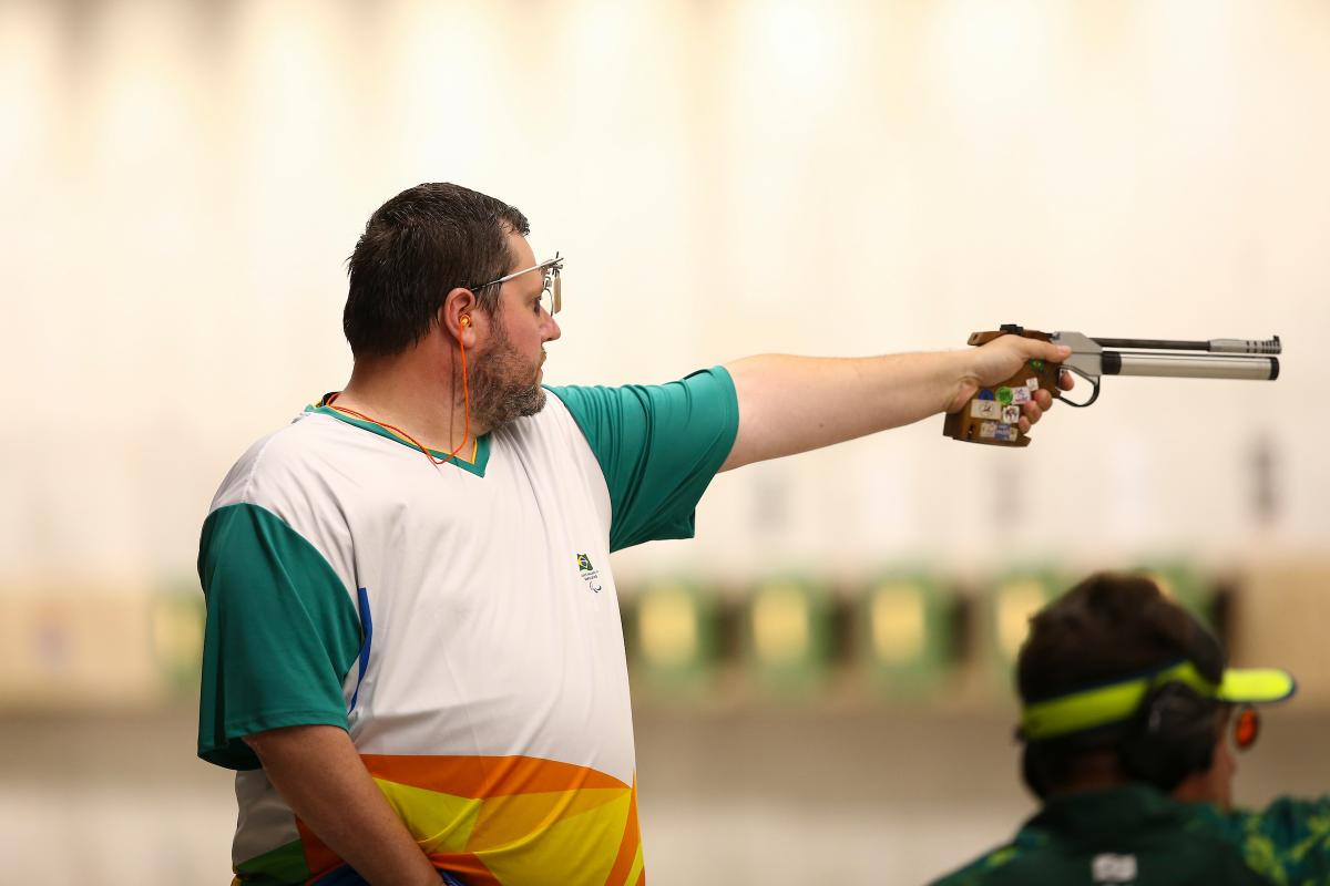 a male Para shooter points a pistol at a target