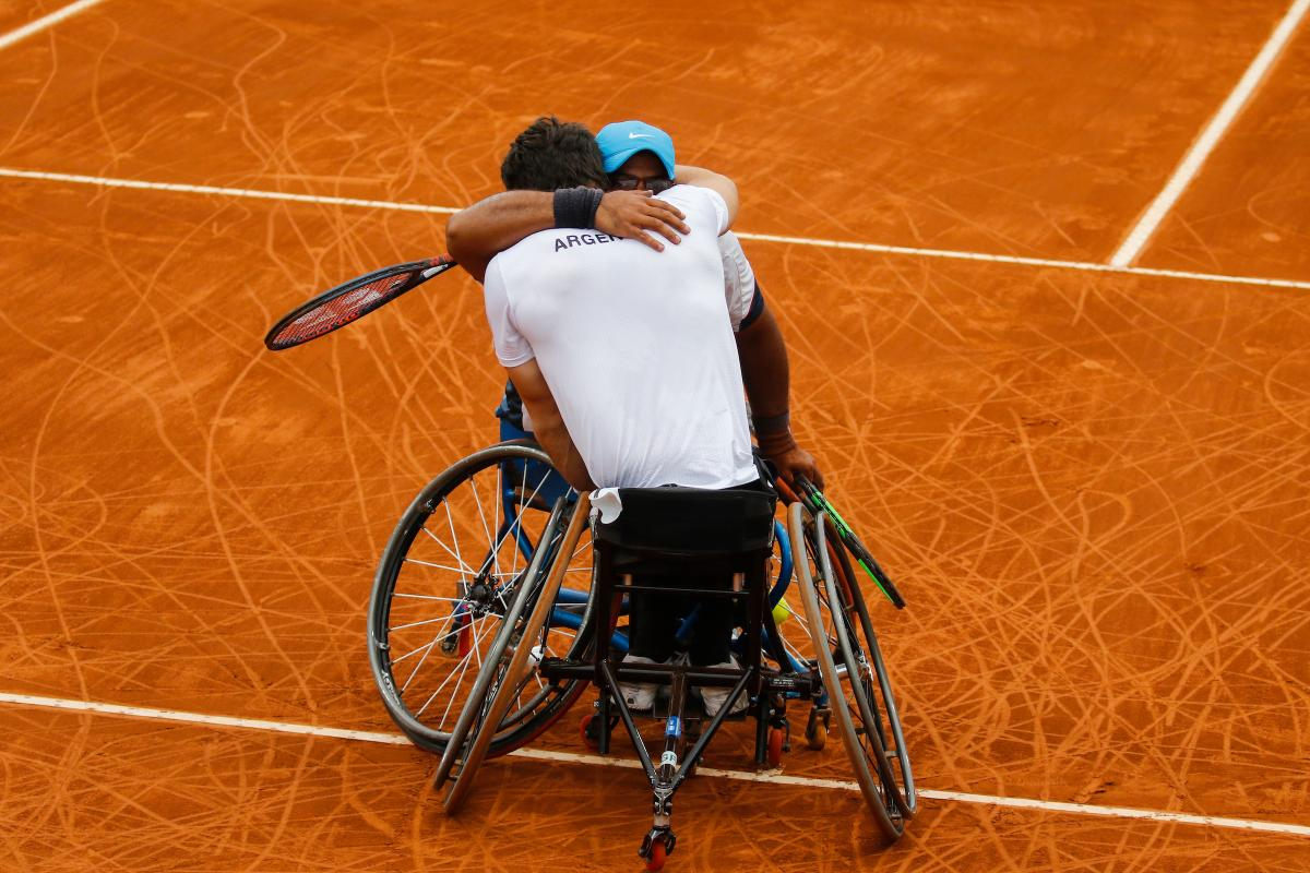 two male wheelchair tennis players hug on the court