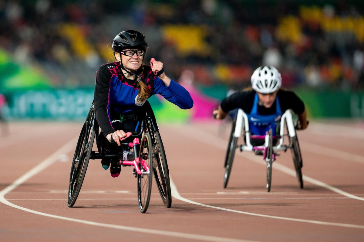 a female wheelchair racer clenches her fist as she crosses the finish line