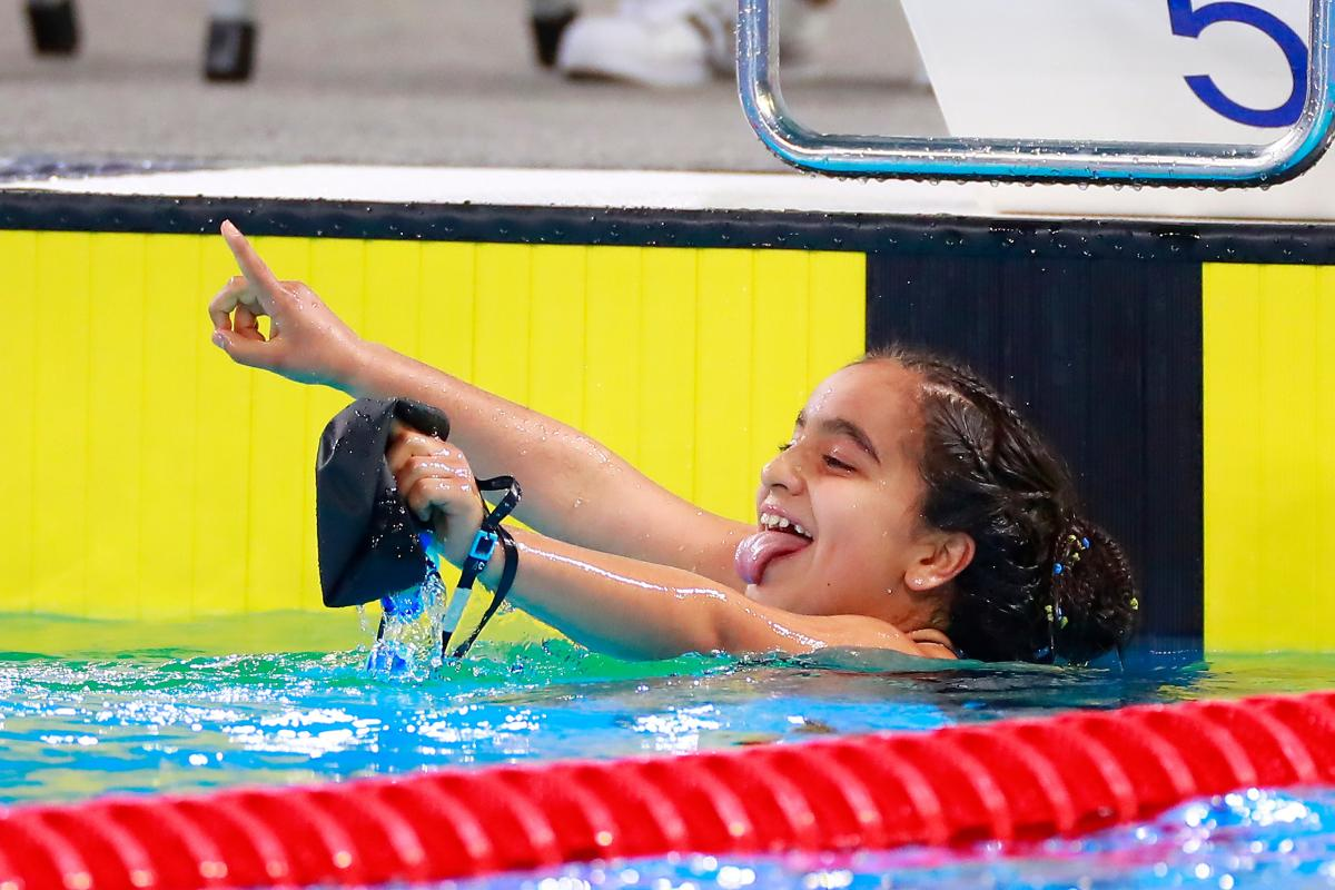 a female Para swimmer in the pool sticks her tongue out
