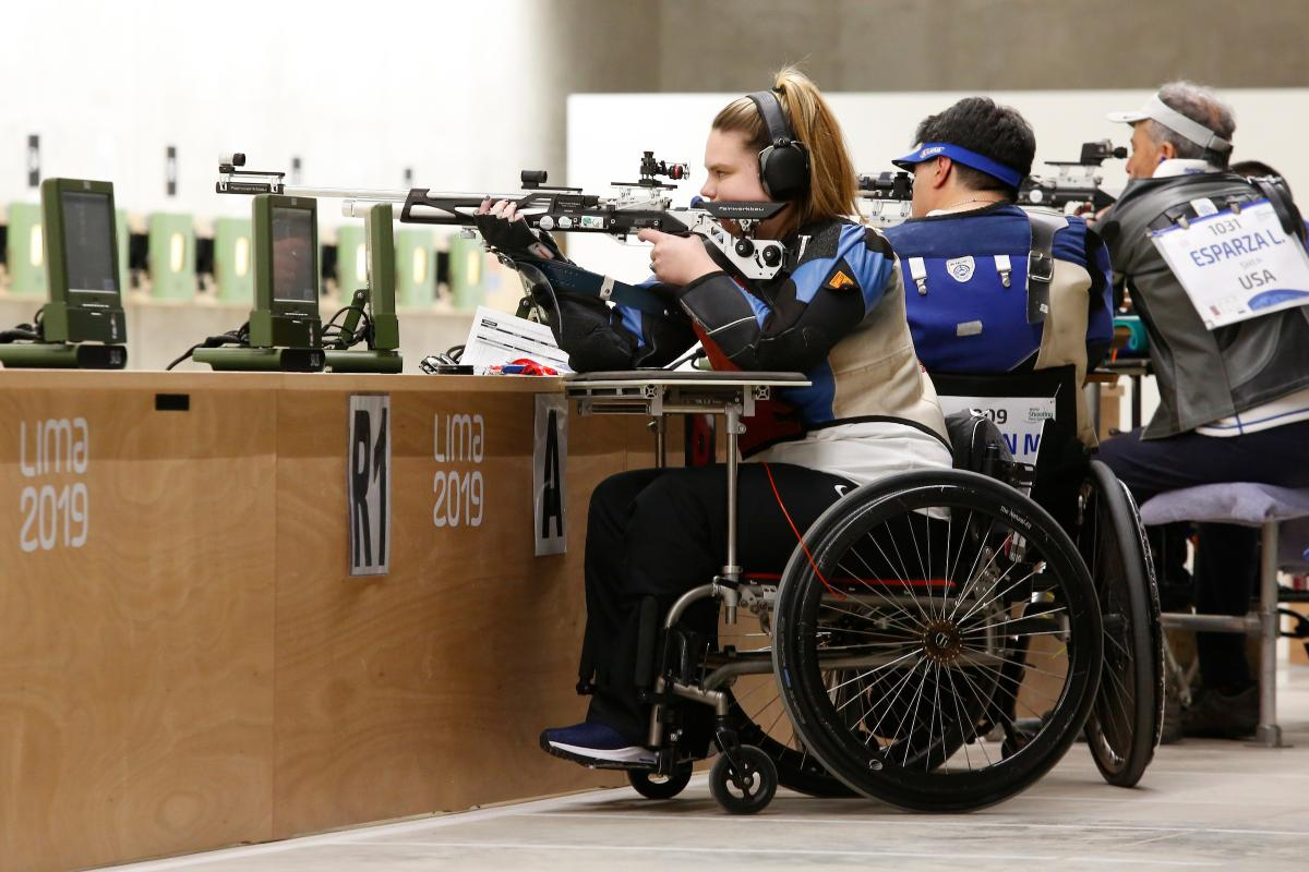 a female Para shooter in a wheelchair fires a rifle at the target