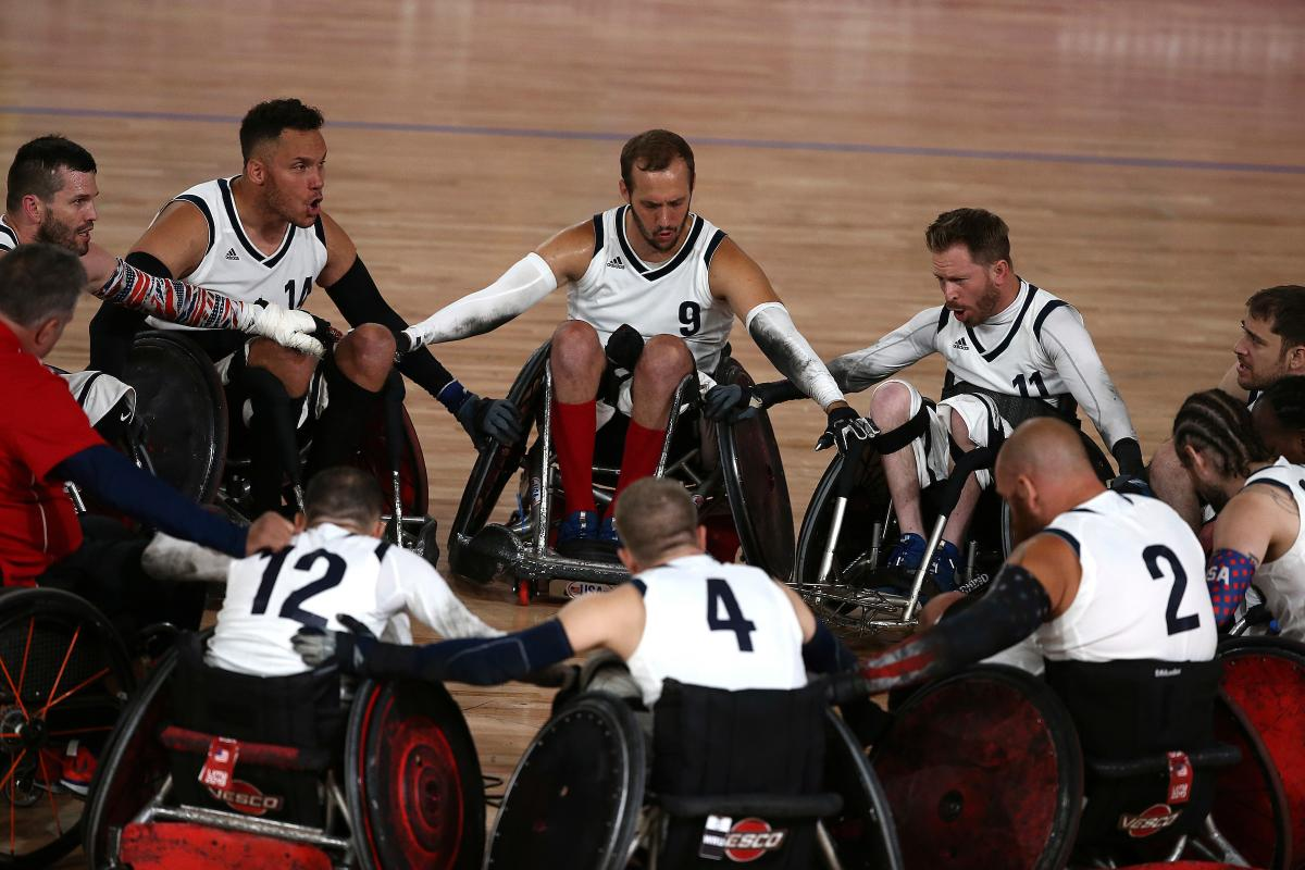 a group of male wheelchair rugby players in a circle holding arms