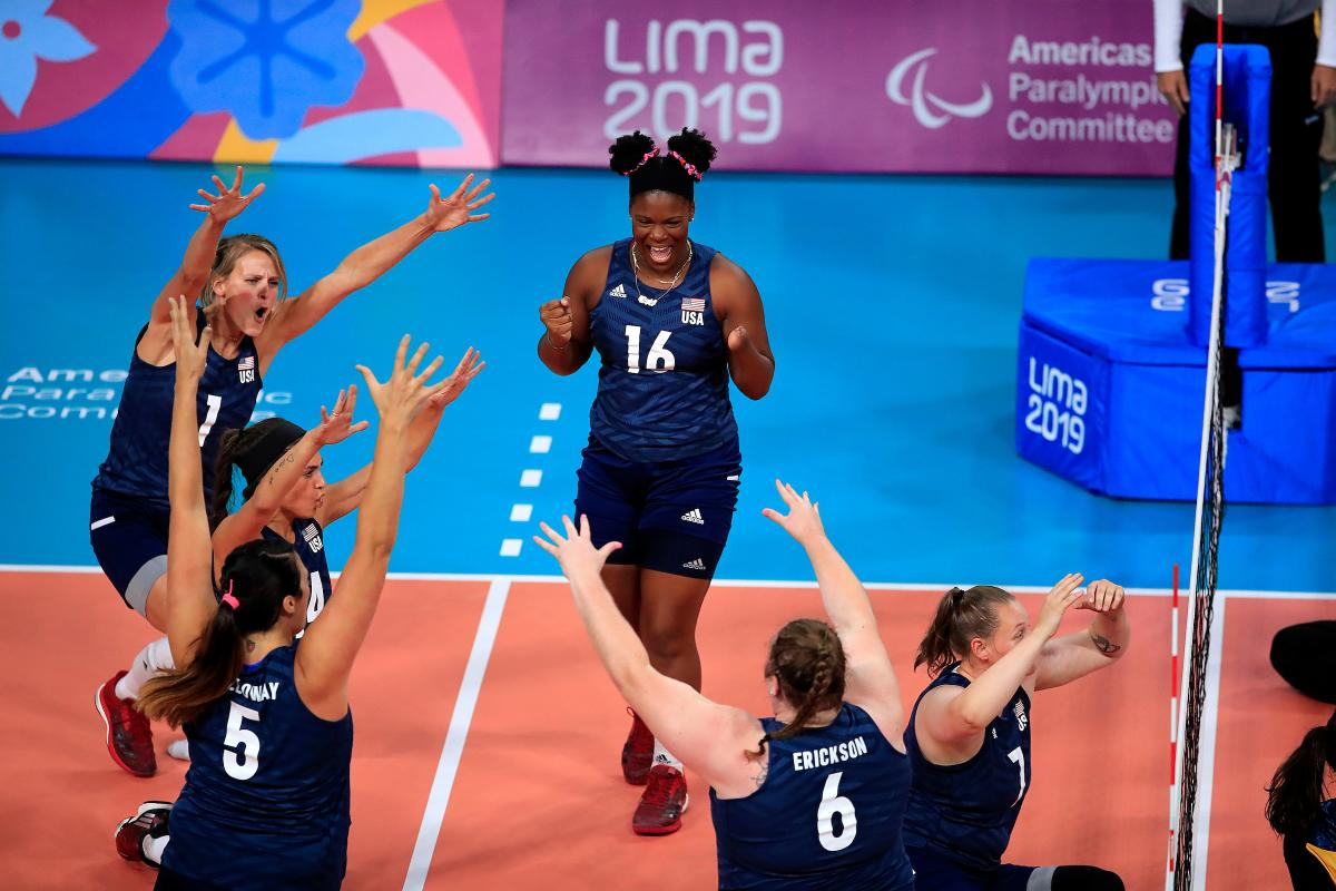 female sitting volleyball players celebrating on the court