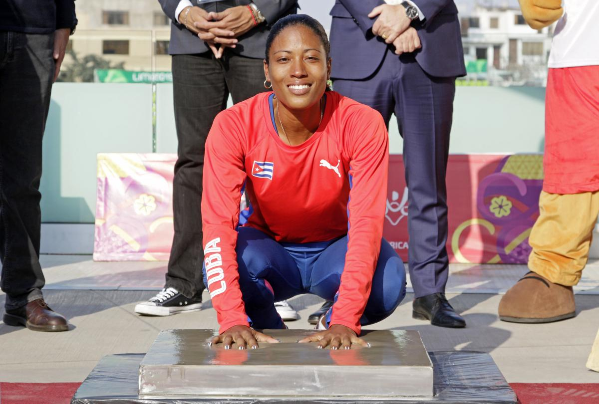 a female Para athlete places her hands in cement to leave prints
