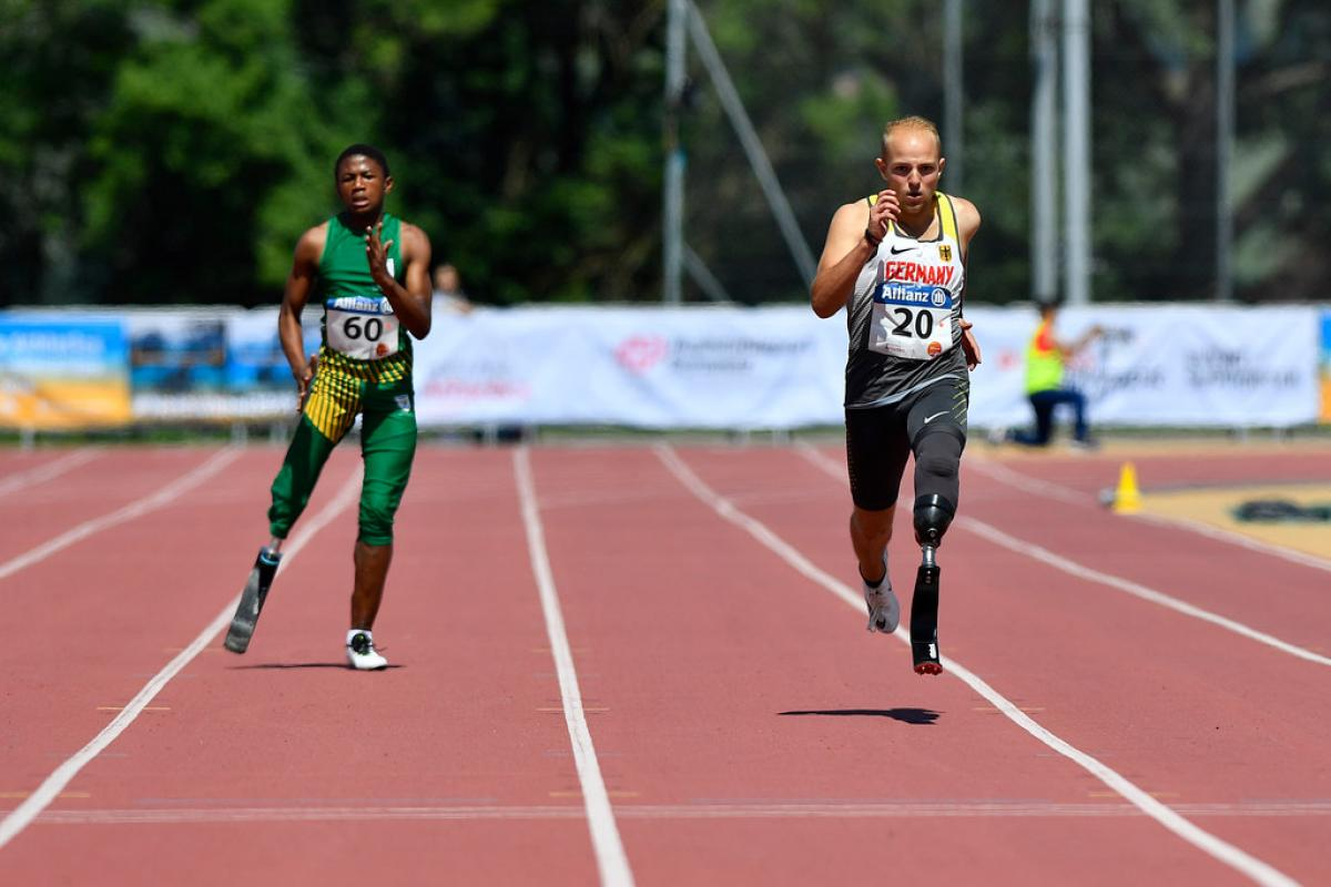 Two male sprinters with prosthesis race side by side