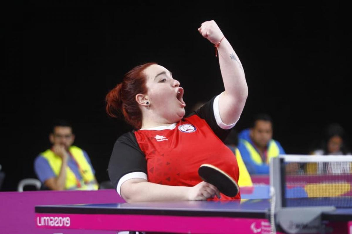 a female wheelchair table tennis player punches the air in victory