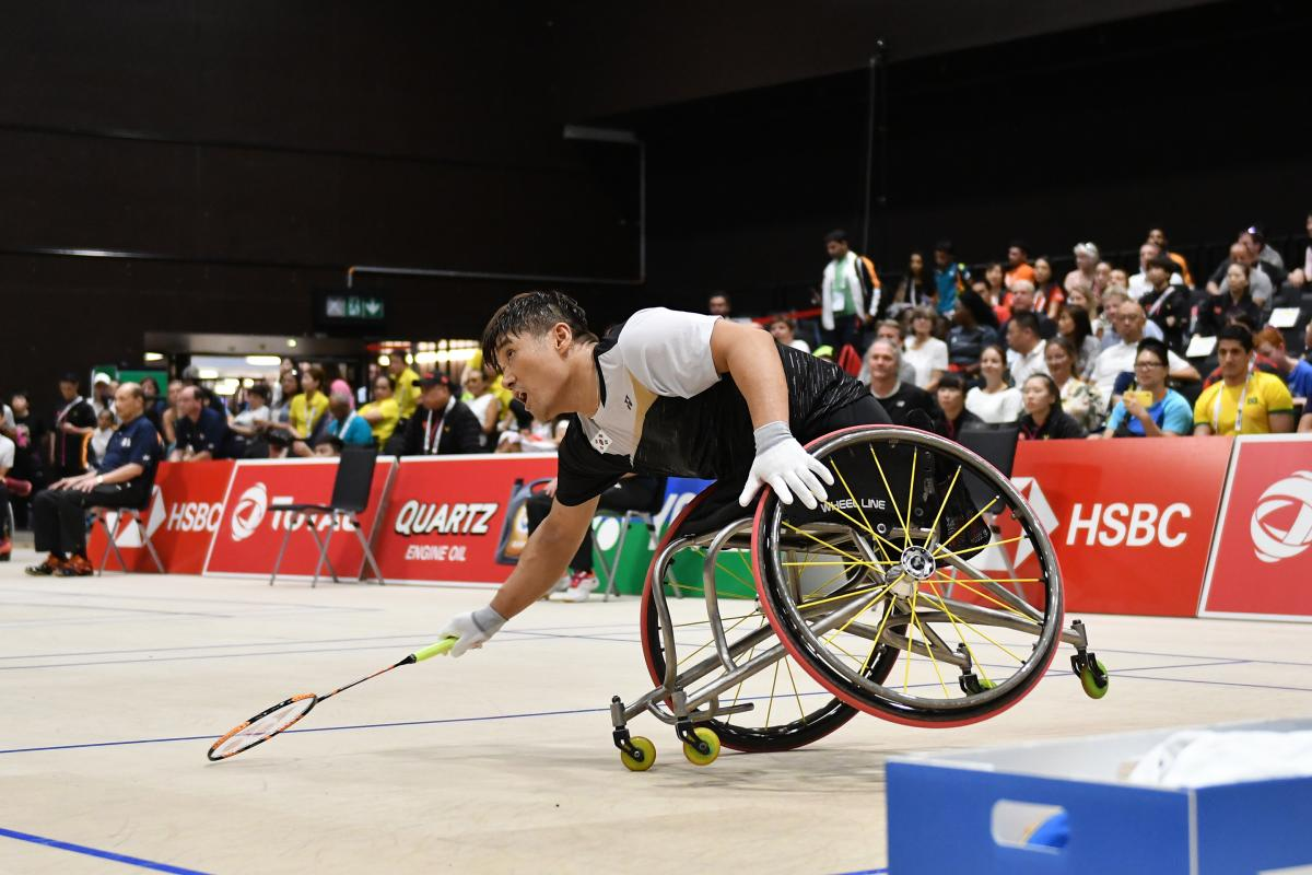 South Korean man in wheelchair leans over to hit the badminton birdie