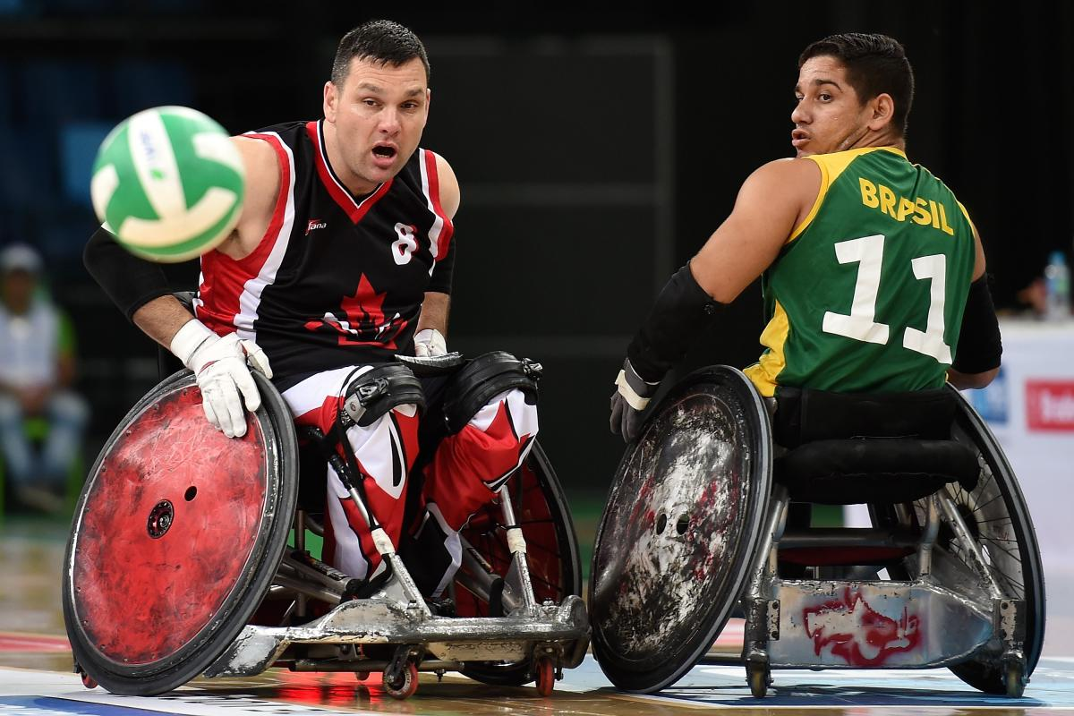 Two male opponents go for wheelchair rugby ball