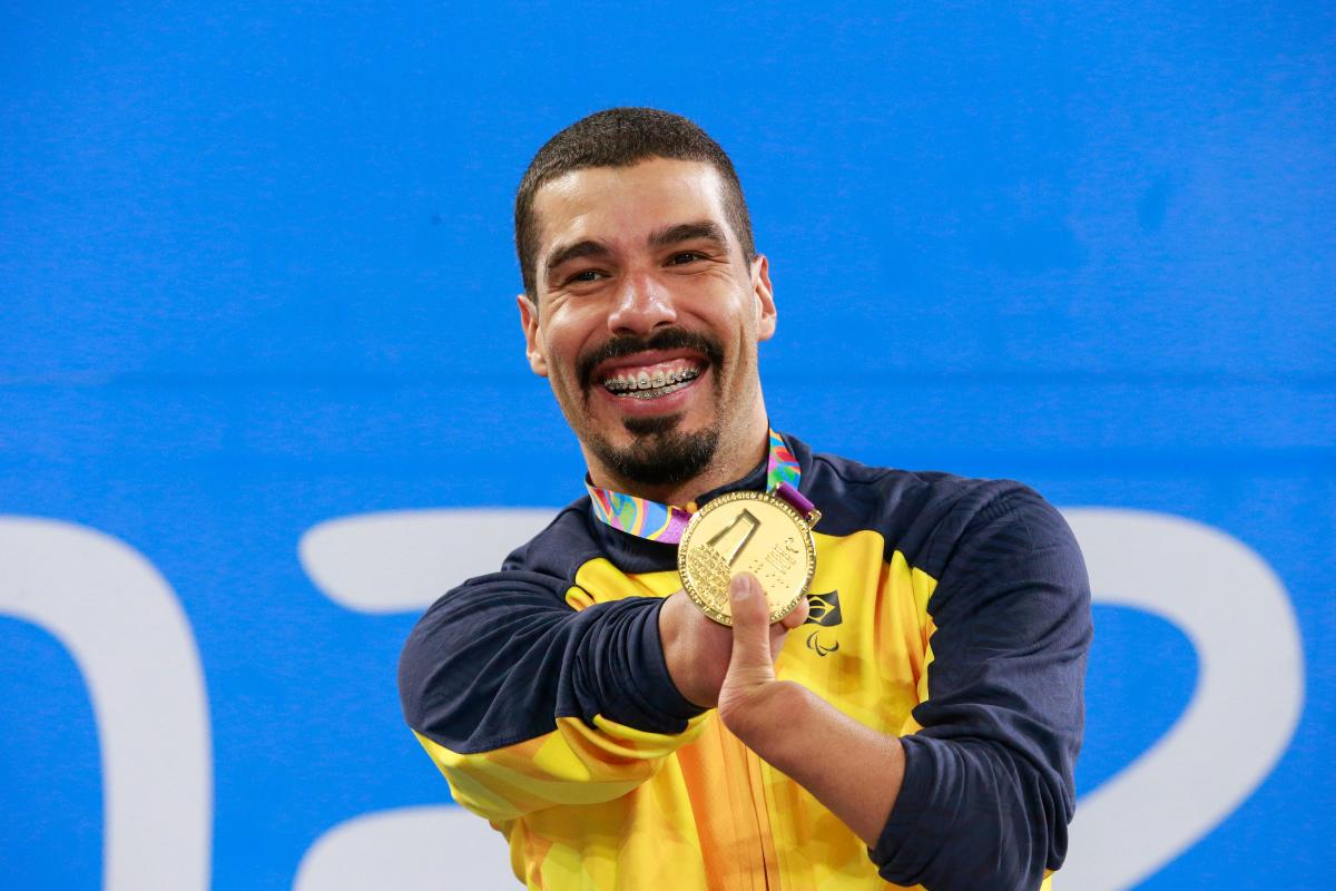 a male Para swimmer holds up his gold medal