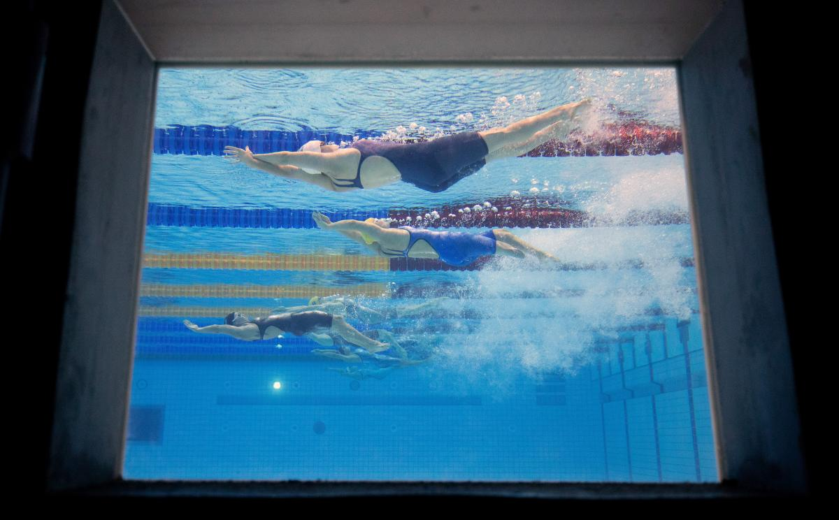 An underwater image of female Para athletes swimming backstroke