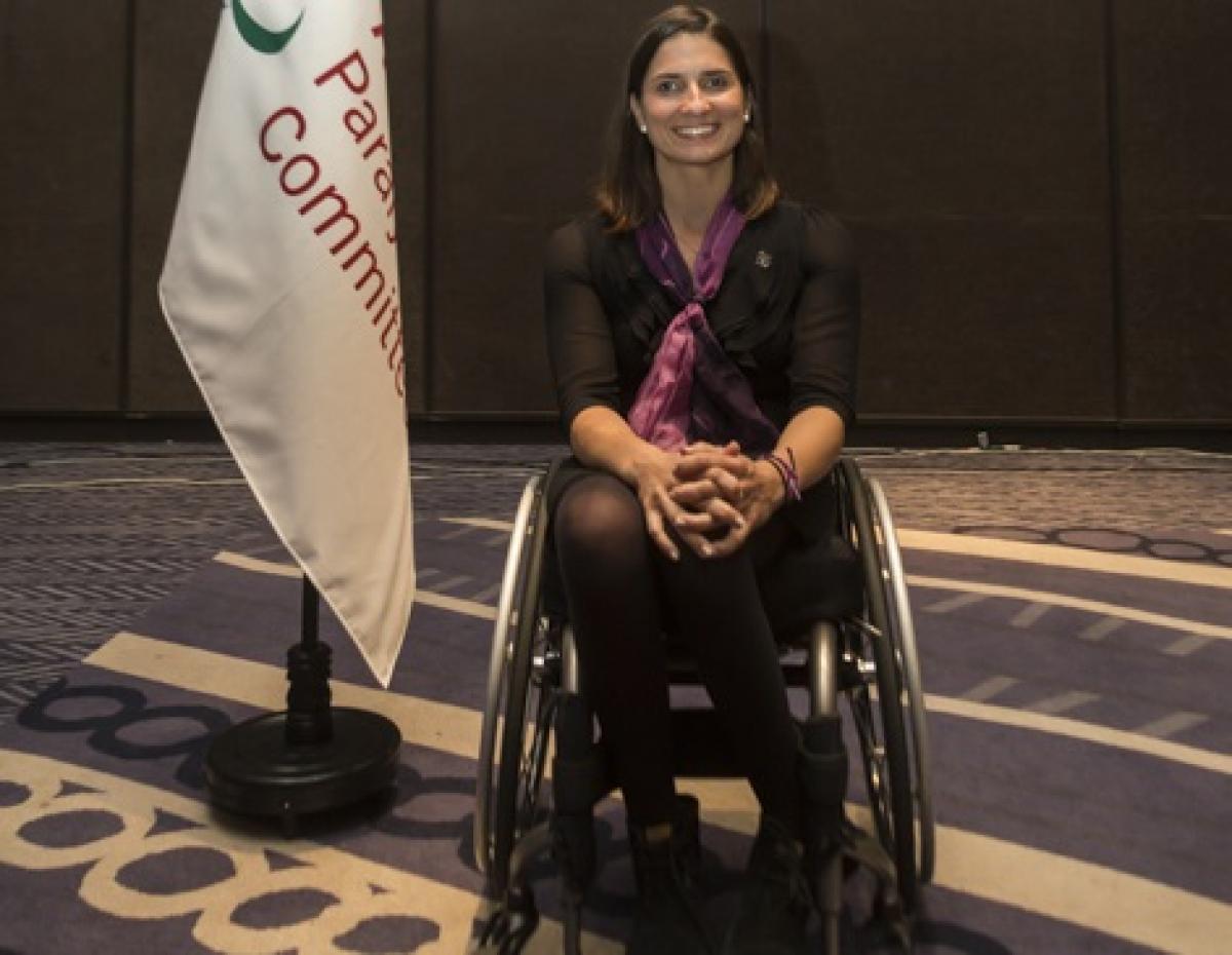 eine Rollstuhlsportlerin neben einer Flagge