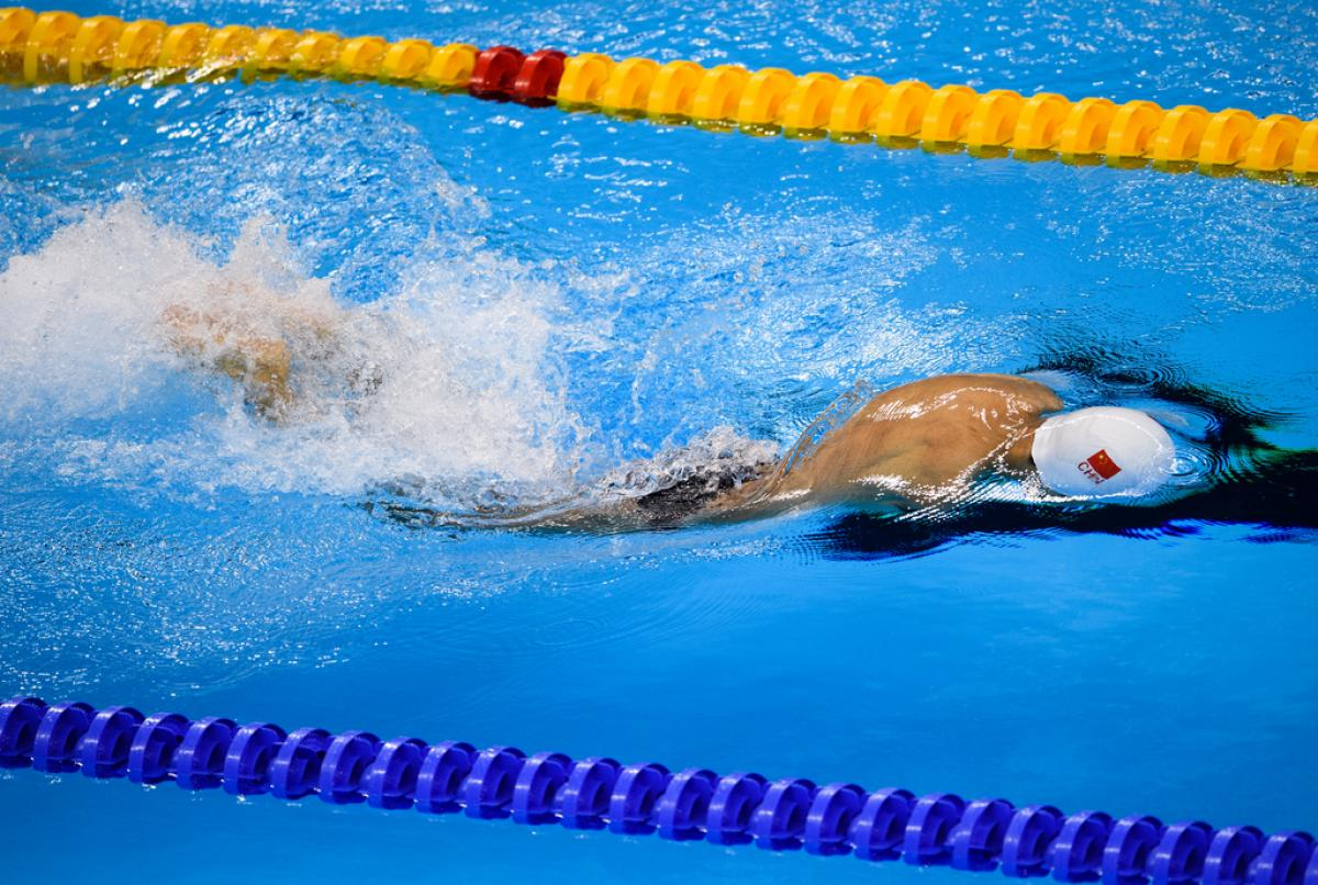a male Para swimmer with no arms does breaststroke in the water