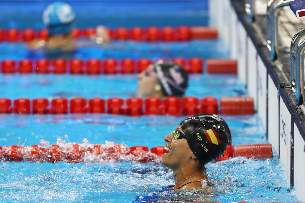 a female Para swimmer celebrates in the pool