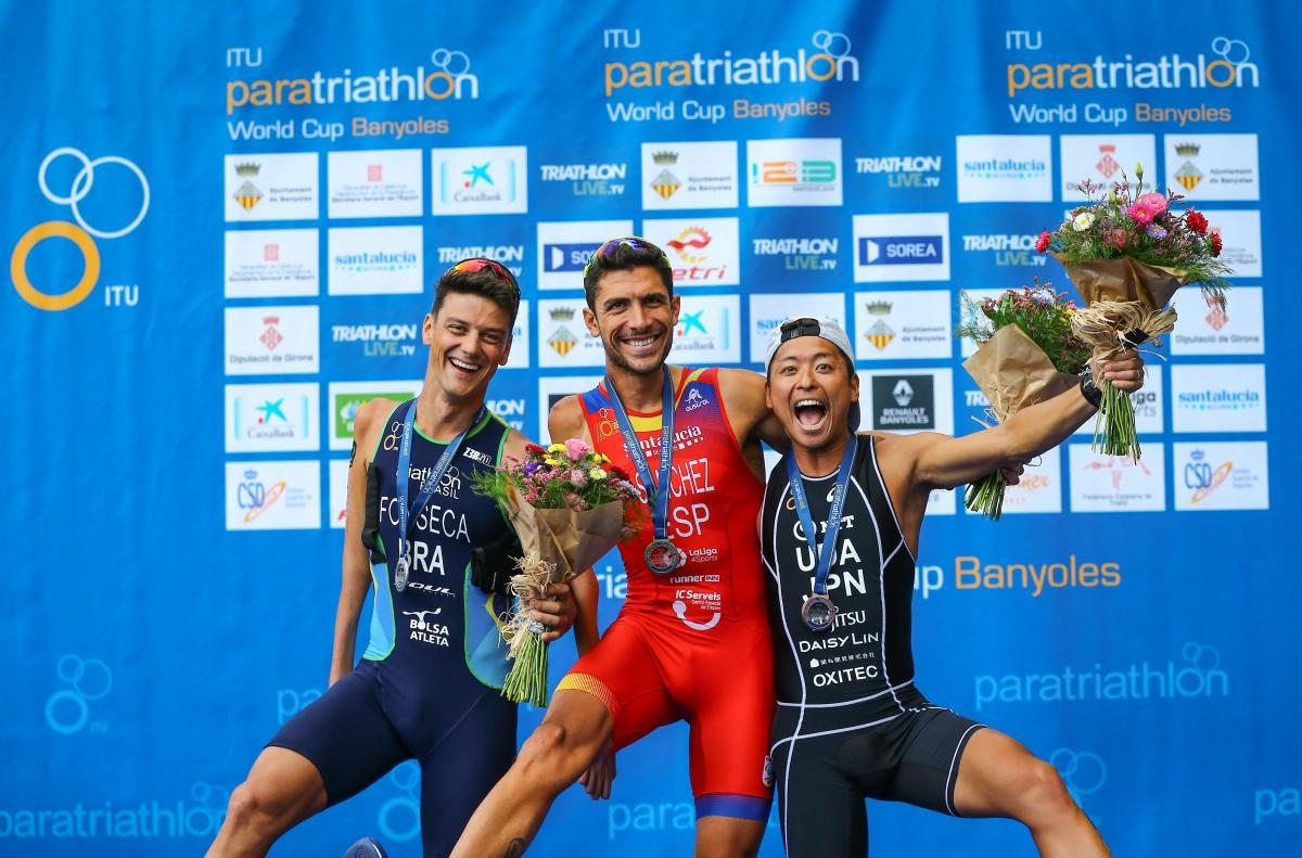 Three male Para triathletes have fun posing for a podium photo