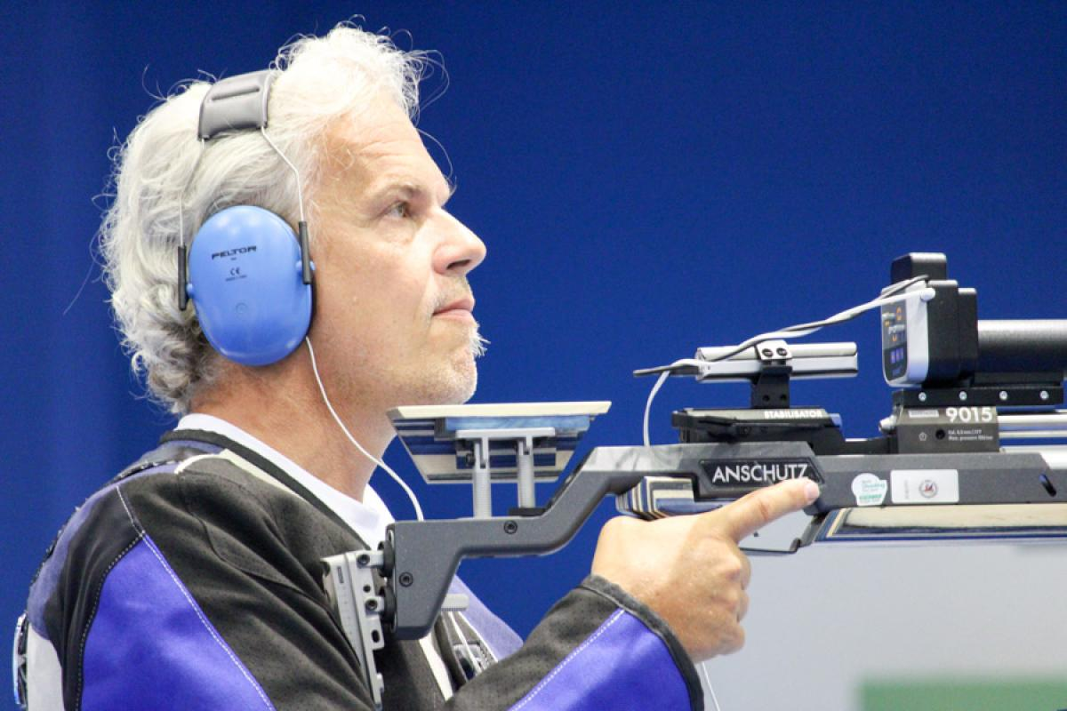 Male vision impaired rifle shooting athlete looks on with noise canceling ear protectors on