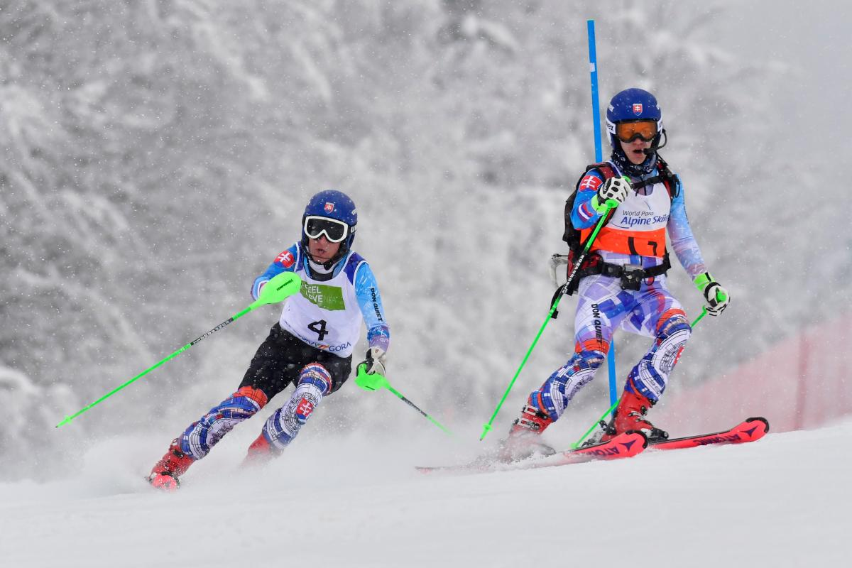 A female guide skier and a male blind alpine skier competing
