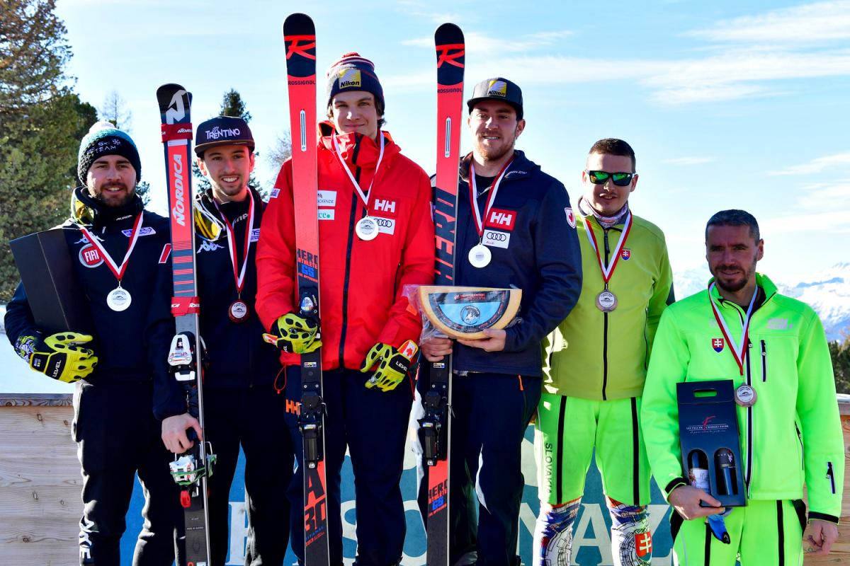 Three vision impaired male skiers with their guides pose on a podium
