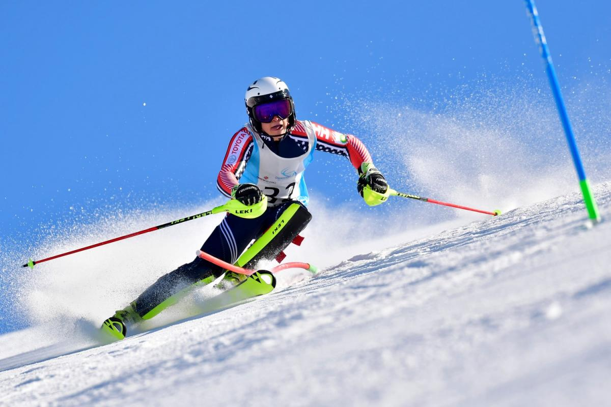Male standing skier makes a turn
