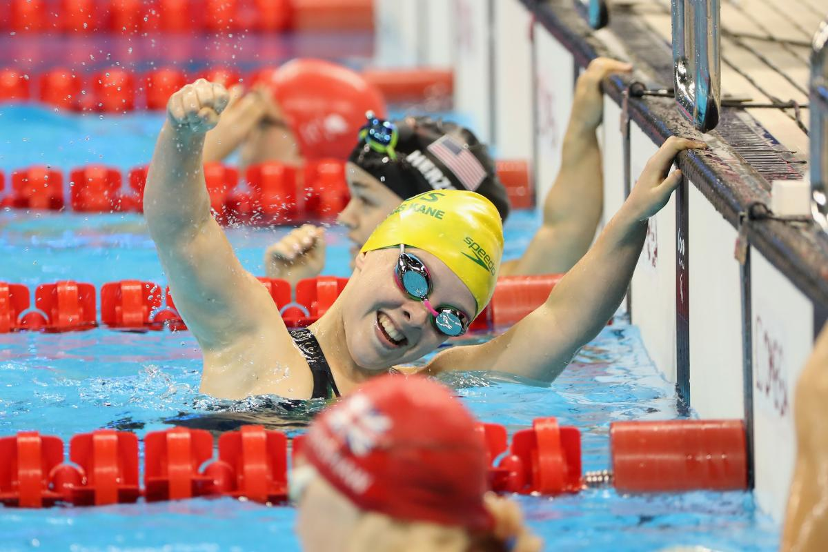 A female Para swimmer celebrating with your hand in the air between two other swimmers