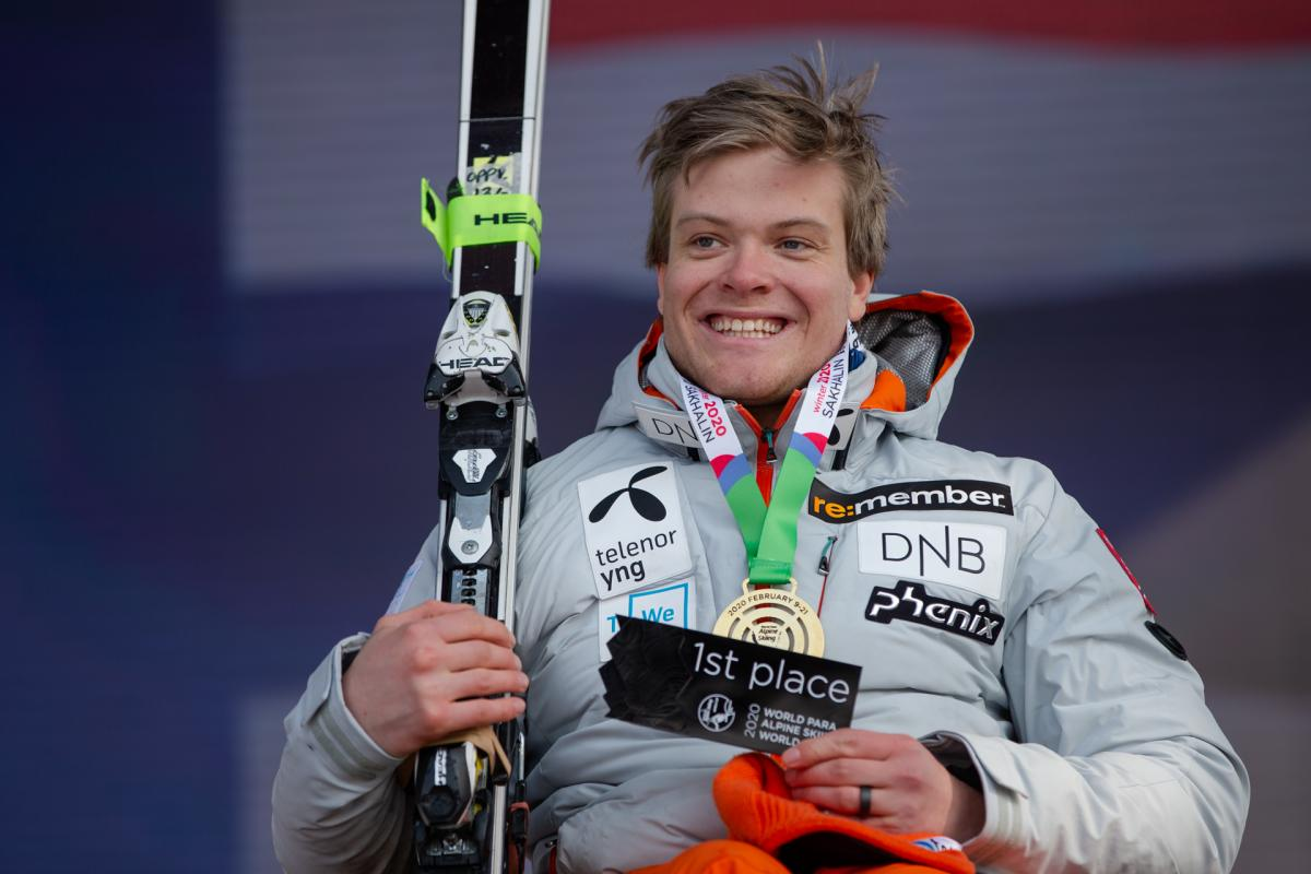 A man with a gold medal smiling and holding a skiing