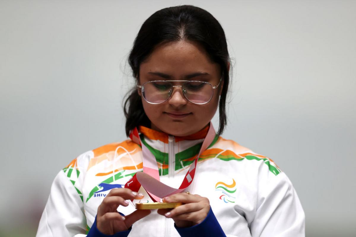 A young woman looking at her gold medal