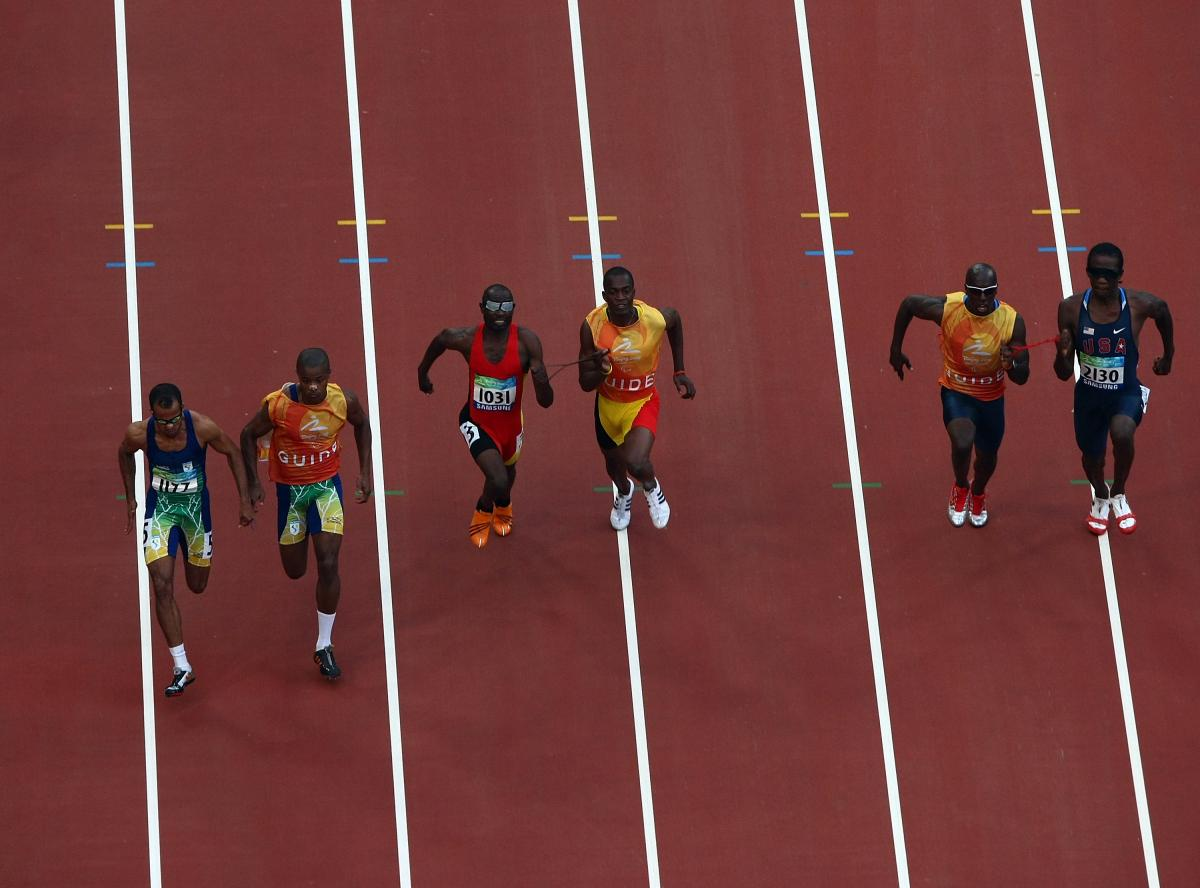 General view of athletes competing in the Men's 100m-T11