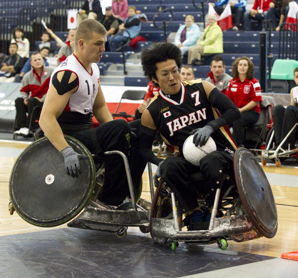 A picture of man in a wheelchair resisting to a choch with another wheelchair.