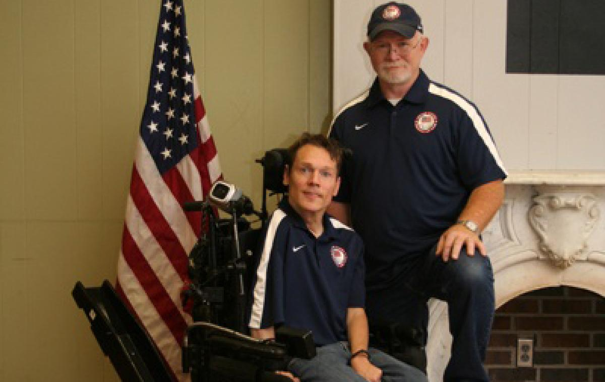 A picture of a man in an electric wheelchair posing for a picture with another man