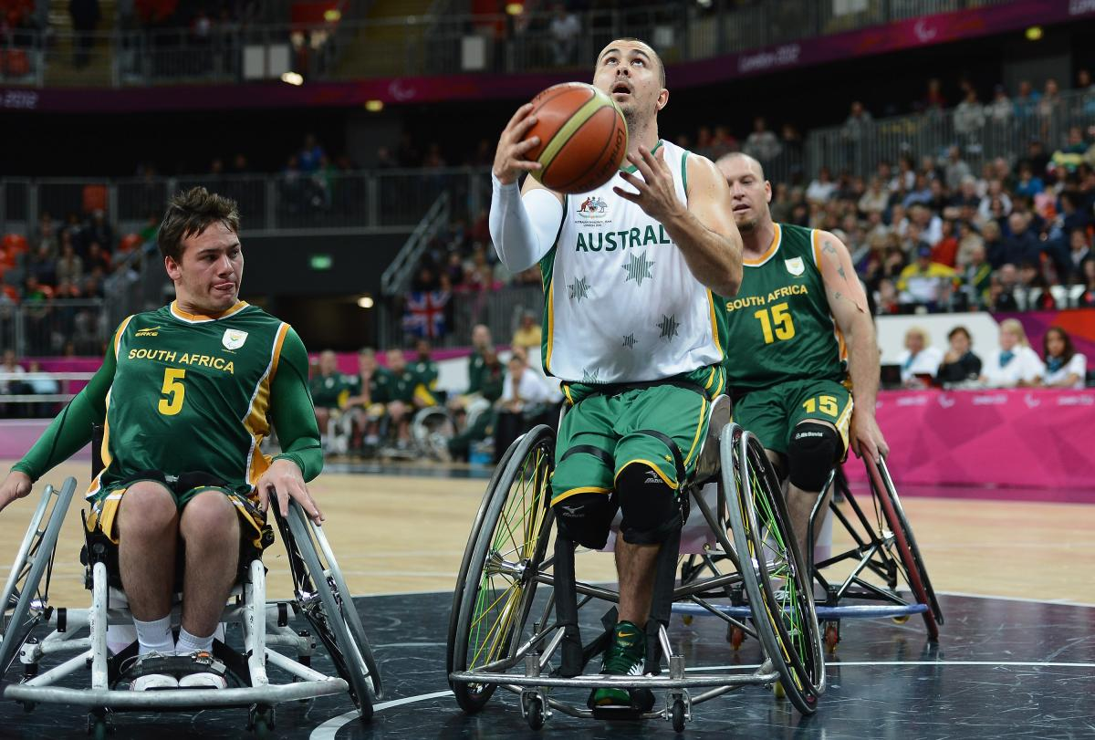 A picture of a man in a wheelchair playing basketball.