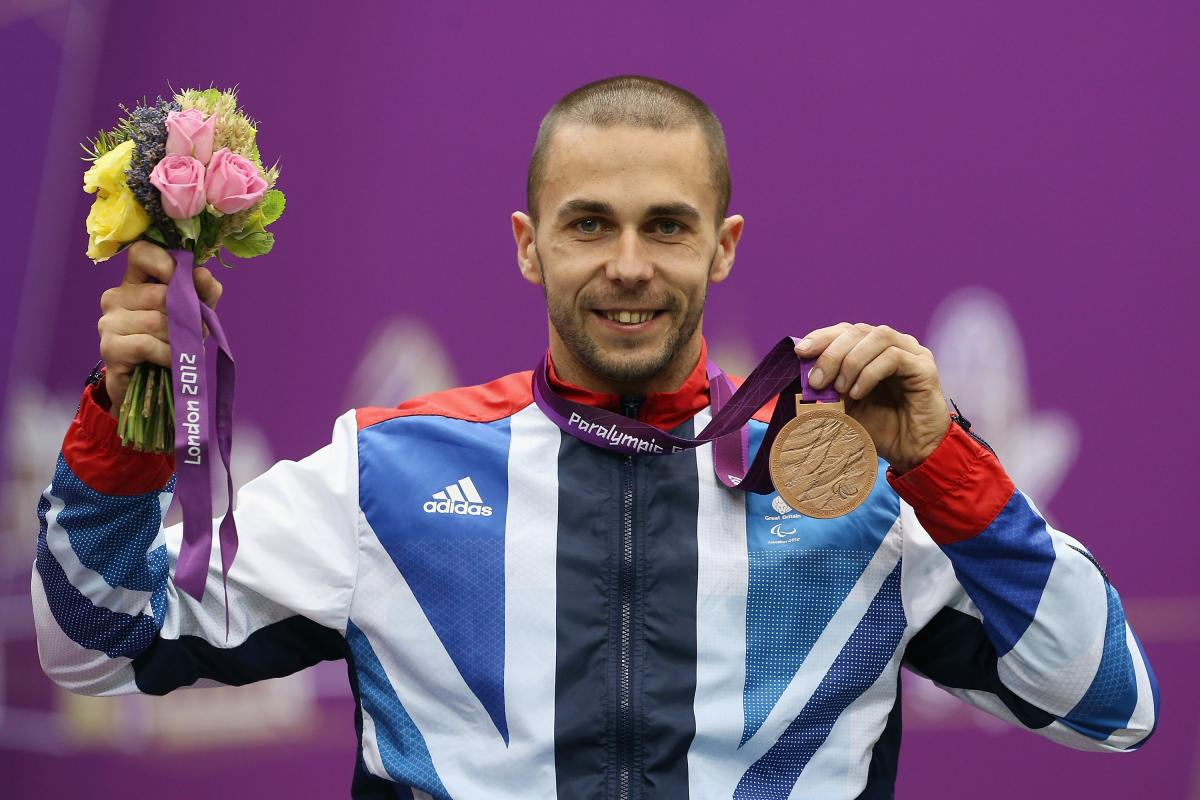 A picture of a man on a podium with a medal around his neck