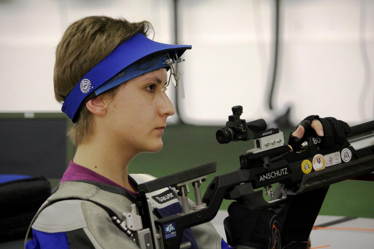 Athlete holding a rifle while practicing shooting.