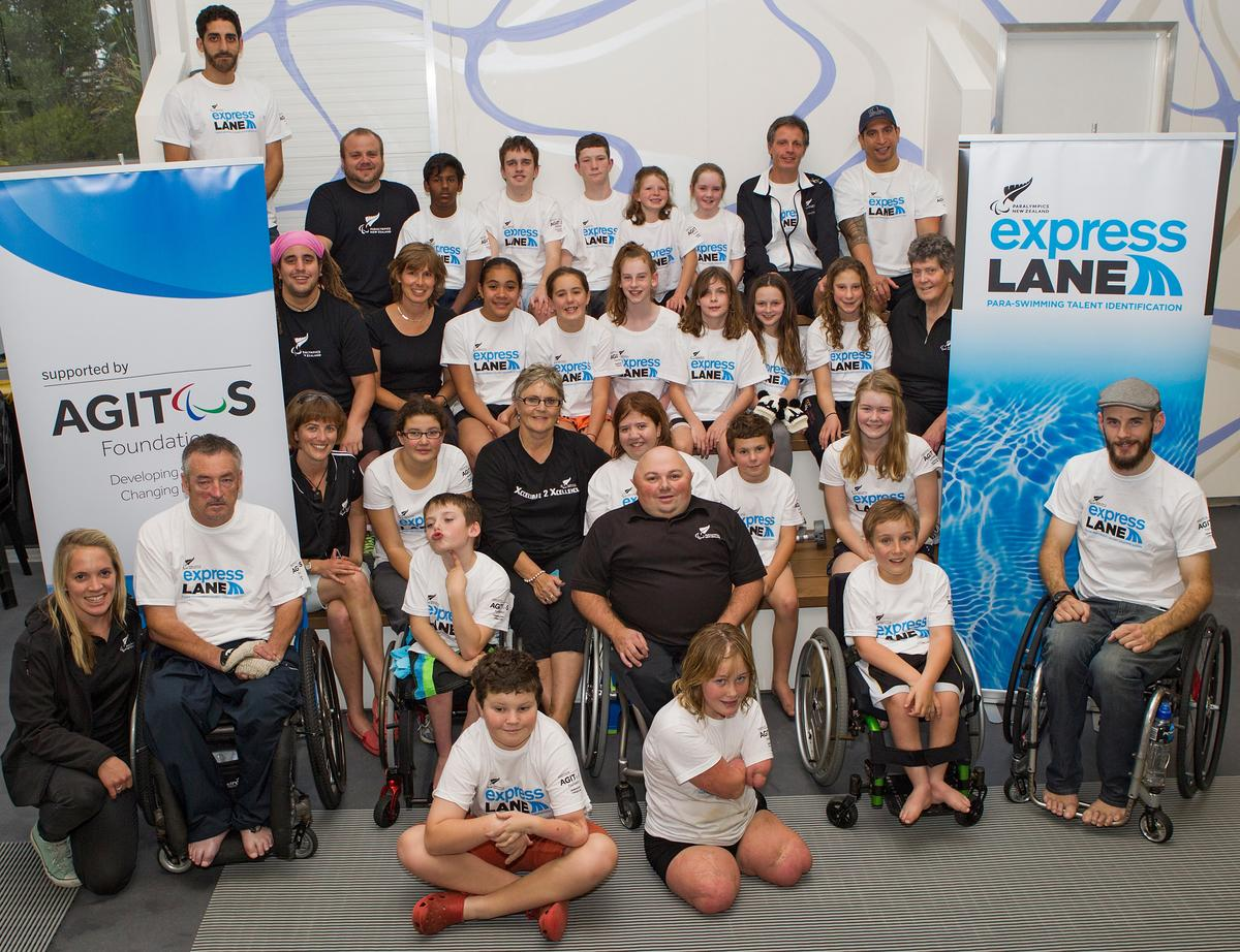 A group of participants pose in front of Paralympics New Zealand and Agitos Foundation banners.
