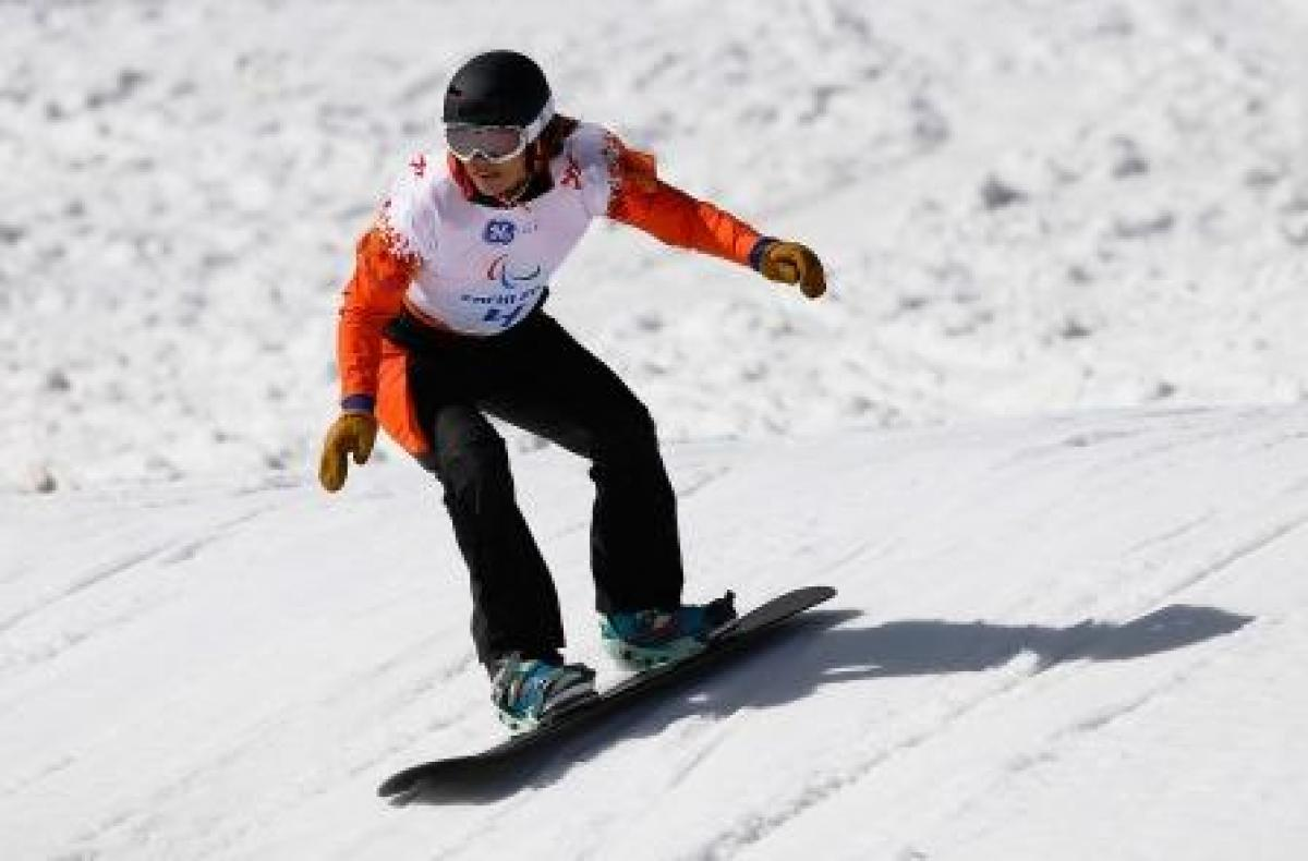 A female snowboarder rides down a slope