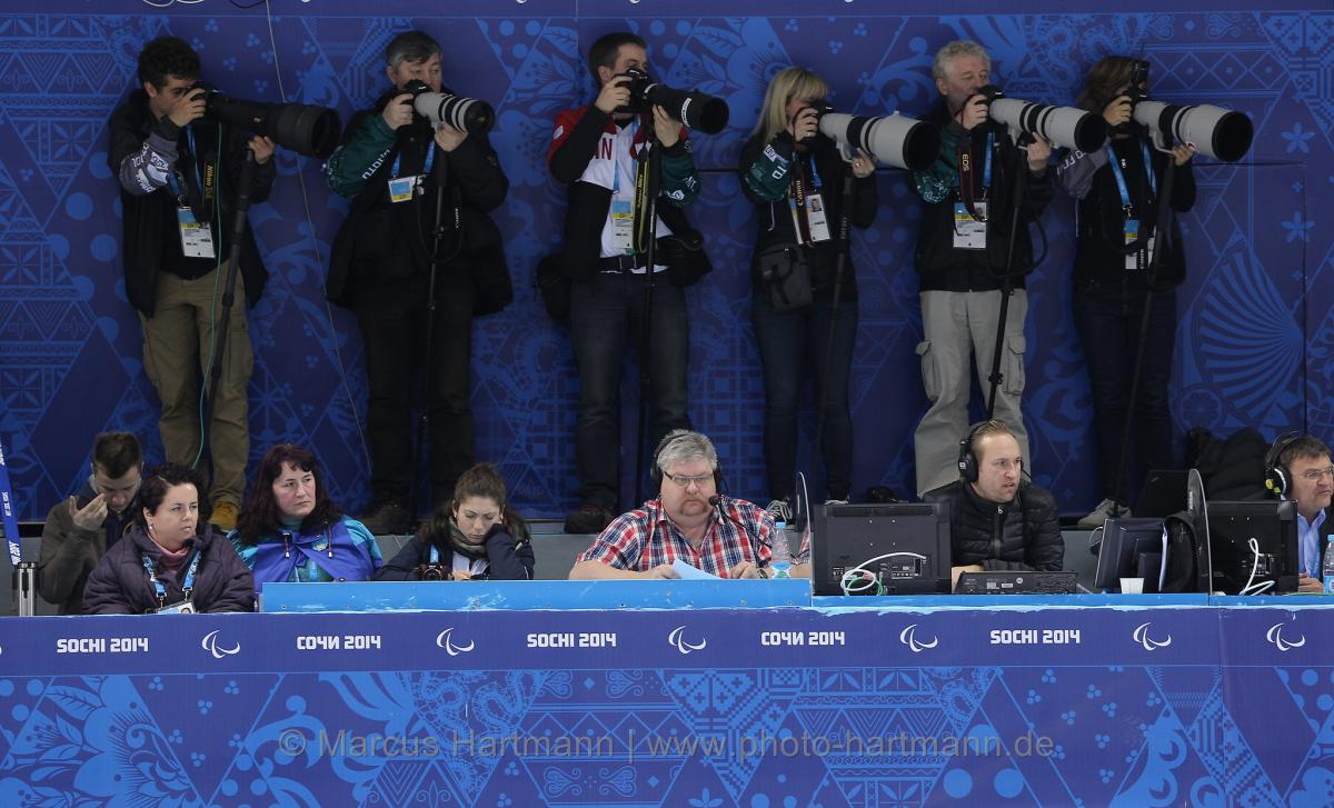 A row of sport photographers taking pictures of ice sledge hockey at Sochi 2014.