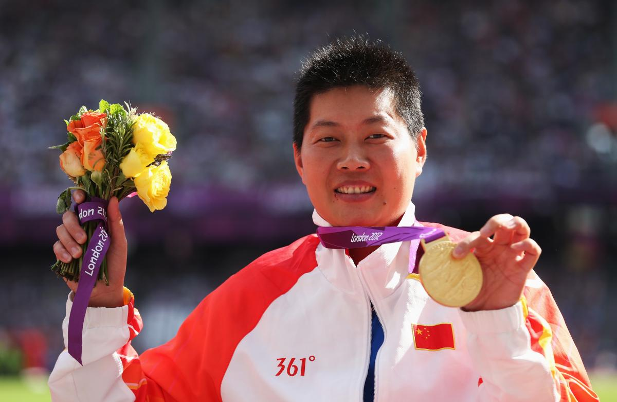 Portrait shot of women showing her medal to the camera.