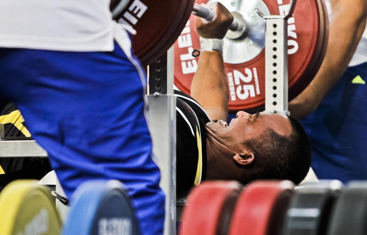 A powerlifter tries to lift the bar.