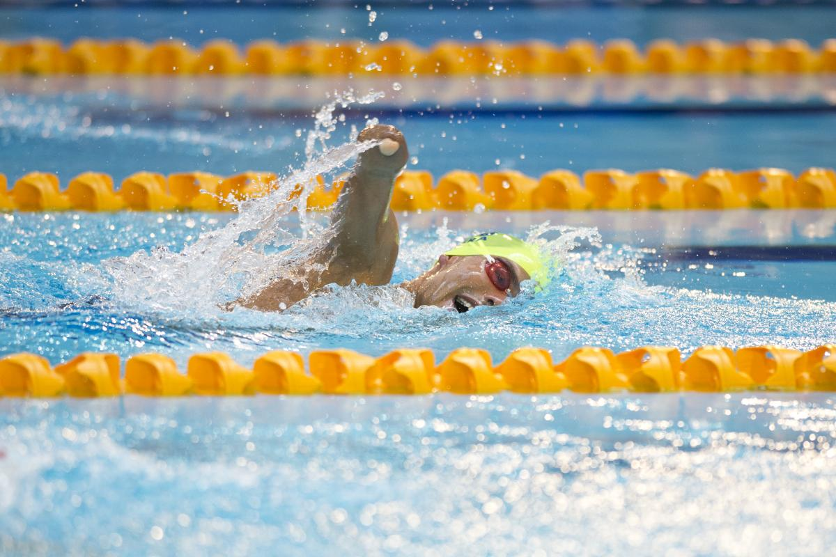 Swimmer with yellow cap doing freestyle.