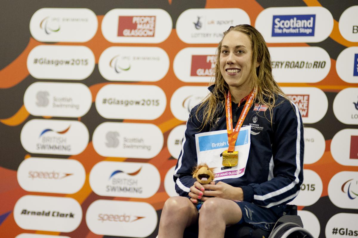 Woman in a wheelchair, on a podium with medal around her neck