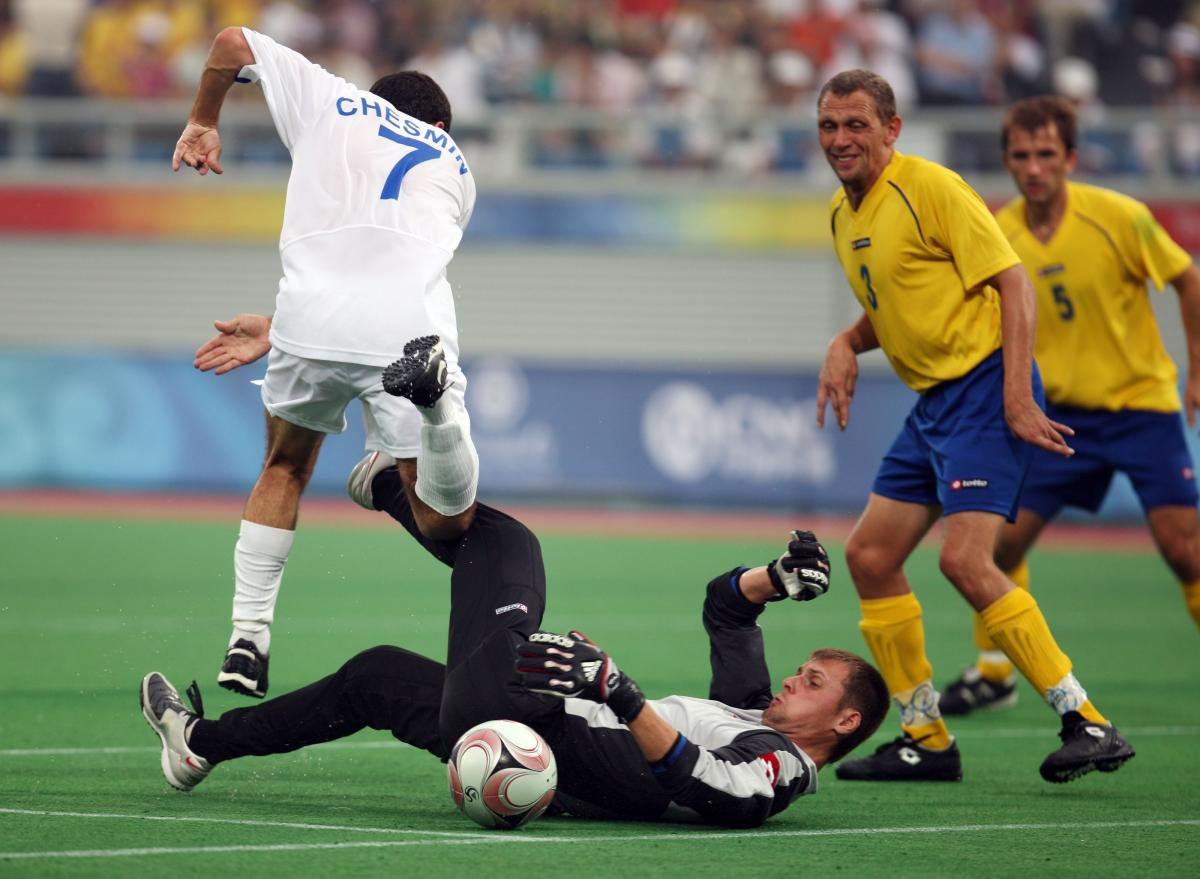 Man on the ground. other man jumping over him. Both focusing on a ball