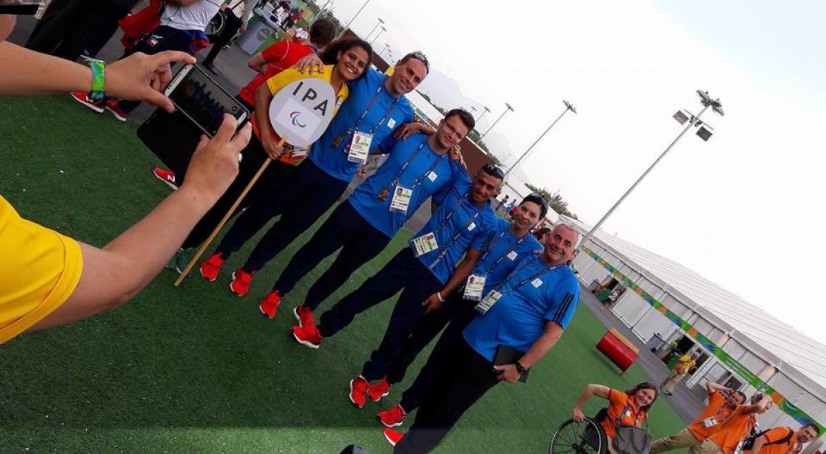 A group of people pose at the Rio 2016 Athlete Village