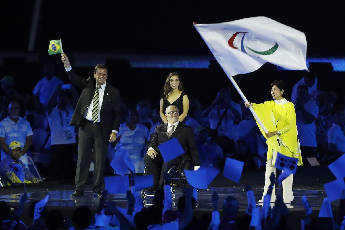 Three people on a stage, one woman waving a flag